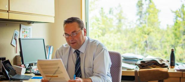 Northwest Territories Minister of INdustry, Tourism and Investment Wally Schumann  works in his office